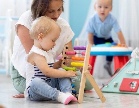 Kids playing on floor with developmental toys in kindergarten. Children have fun in nursery or daycare. Babies with teacher in creche