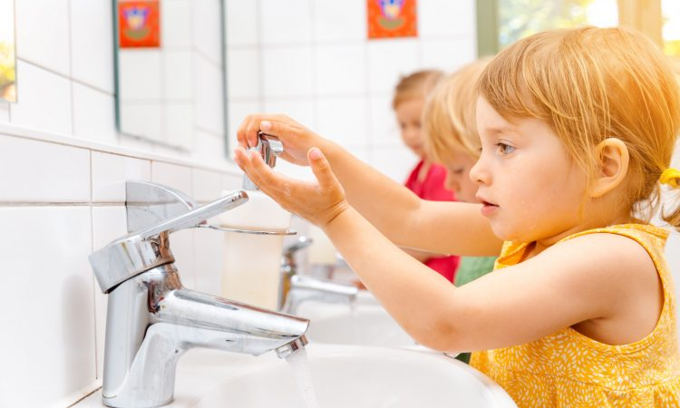 Child in kindergarten washing her hands in bathroom