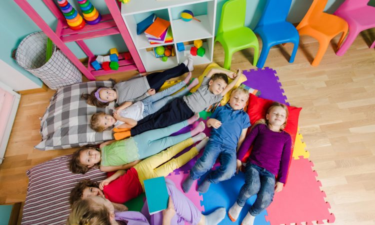Young attractive teacher reading story before the naptime at the kindergarten. Lovely kids laying on a floor on soft mats and pillows. Time to have a rest and to calm down. Top view.